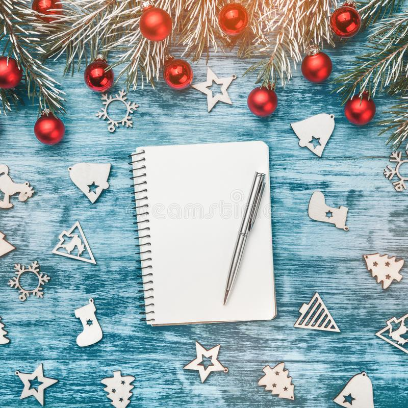 Blank notebook and pen on blue background of fir branches, shiny red baubles and ornamented wooden toys. Top view stock images