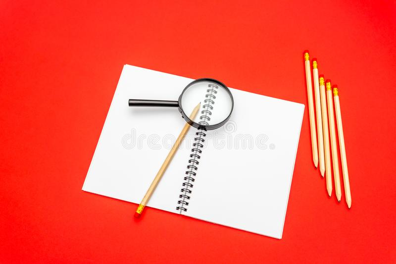 Blank notebook and pencil on red background. Magnifying glass on top of notepad.  royalty free stock image