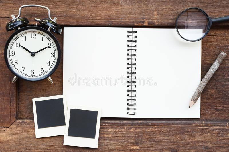 Blank notebook, photo frame, pencil, magnifying glass and clock royalty free stock photos