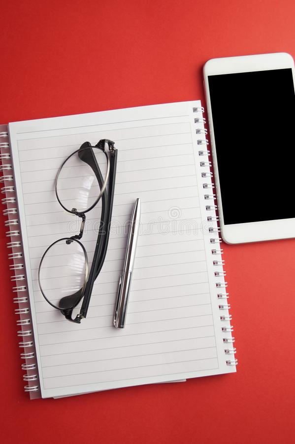 Blank notebook with smart phone on desk. From above royalty free stock photo