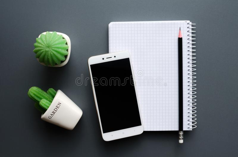 Blank notebook with smartphone on grey office desktop. Blank opened white notebook with pen, black screen smartphone and cacti potted on grey office desk royalty free stock photos