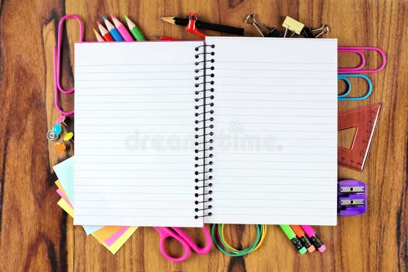 Blank notebook with underlying frame of school supplies over wood royalty free stock images