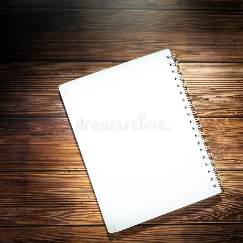 Blank notebook on wooden table. Opened notepad on top of a desk. stock photo