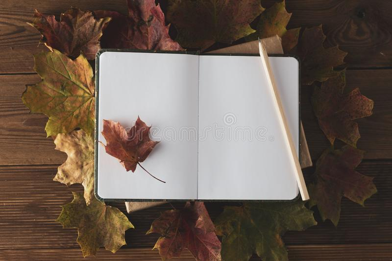 Blank notebook on a wooden work table with autumn leaves. Top view. Copy space royalty free stock photos