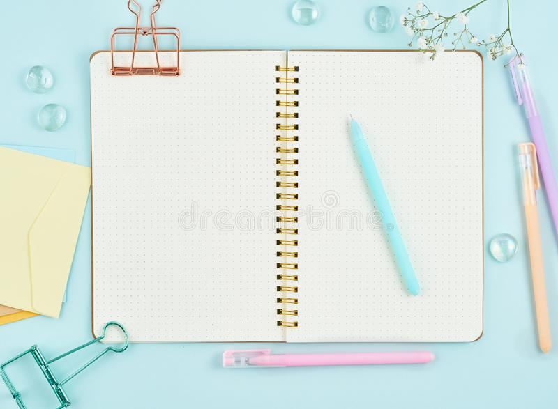 Blank notepad page in bullet journal on blue office desktop. Top view of modern bright table with notebook and flower. Mock up, royalty free stock images