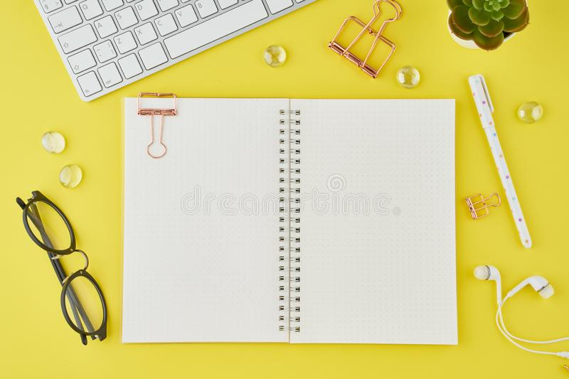 Blank notepad page in bullet journal on bright yellow office desktop. Top view of modern bright table with notebook, stationery. stock photos