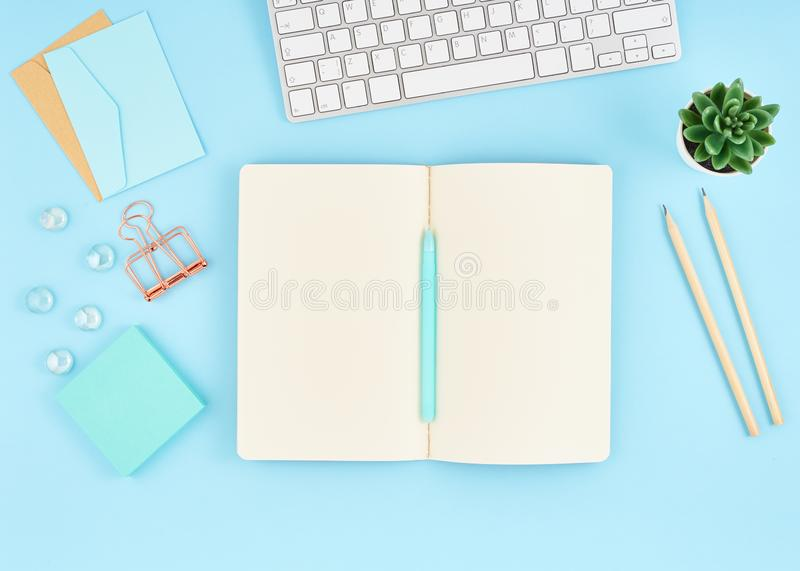 Blank notepad page for text on blue office desktop. Top view of modern bright table with notebook, keyboard. Mock up, copy space stock images