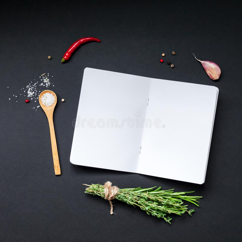 Blank notepad pages with greens herbs and spices. Flat lay overhead view blank notebook pages mockup text space invitation card on black background with greens stock image