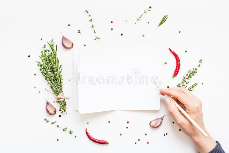 Blank notepad pages with greens herbs and spices. Flat lay overhead view blank notebook pages mockup text space invitation card on white background with greens royalty free stock photo