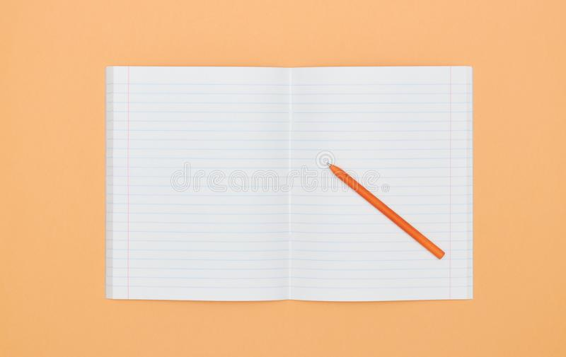 Blank Notepad with pen on orange peach background. The View From The Top. school subjects and education. white sheet in notebook. stock photo