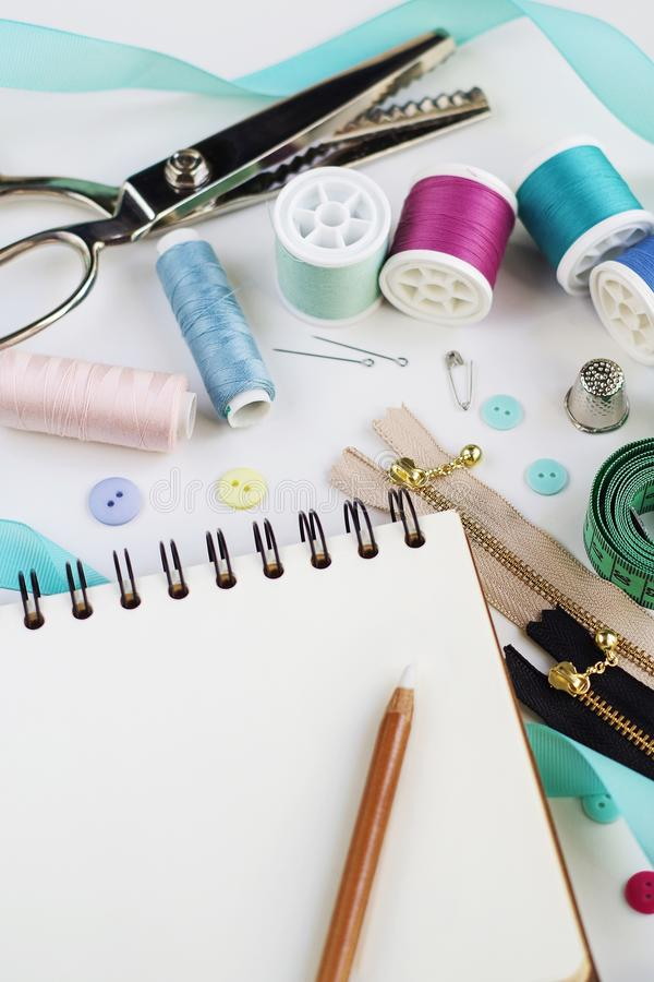 Blank notepad with pencil surrounded with spools of thread and basic sewing tools including pins, needle, a thimble stock photography