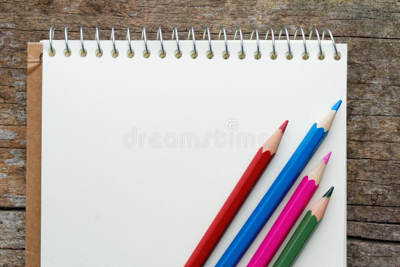 Blank notepad with red,blue,pink and green colour pencils on wooden table. royalty free stock images