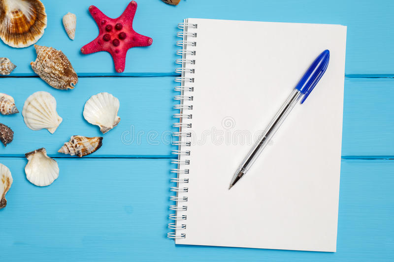 Blank notepad and Sea star and shells on wooden blue background. royalty free stock photo