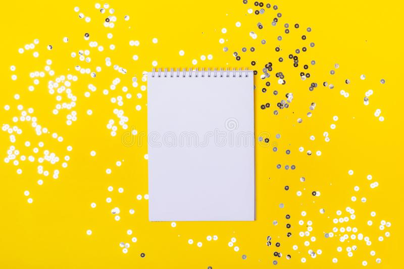 Blank notepad on yellow background with sparkles. Place for any list - plans, totals, successes.  royalty free stock image