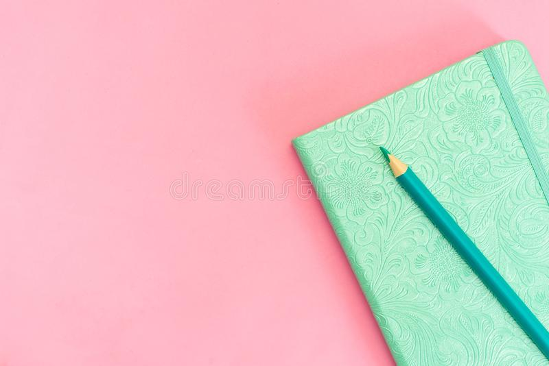 Blank notepad with yellow pencil on pink and blue background royalty free stock photography