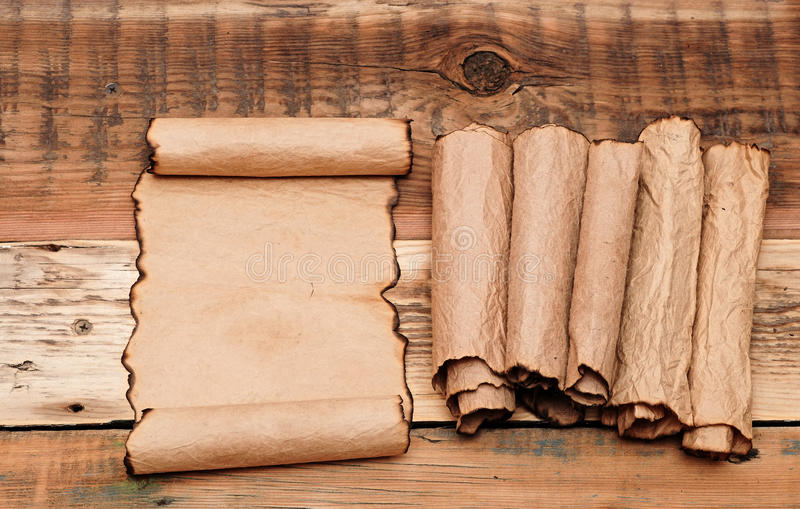 Blank old sheet paper. With pile scrolls on old wooden background stock image