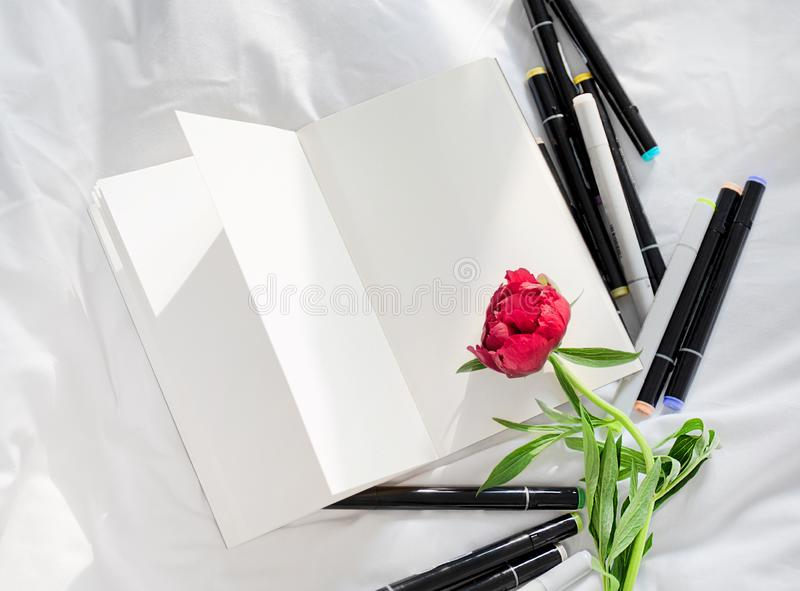 Blank open diary on a white bed with pile of pens royalty free stock photography