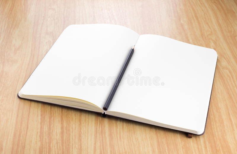 blank open notebook with black pencil on wood table,Business template mock up for adding your text royalty free stock images