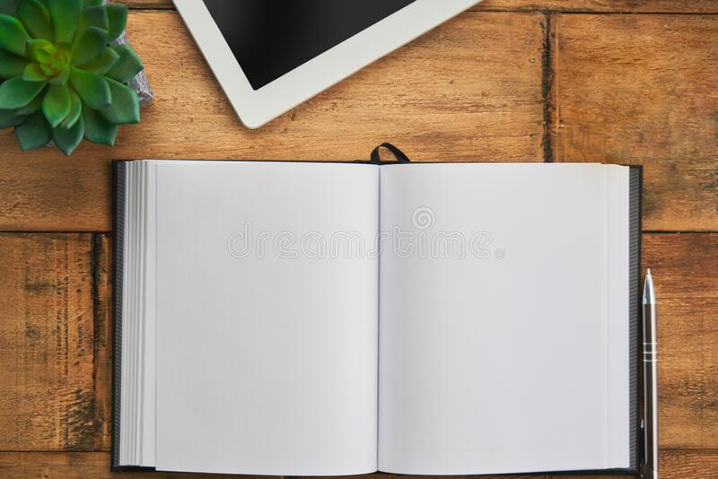 Blank open notebook with tablet wooden table, desktop. Top view image.  royalty free stock image