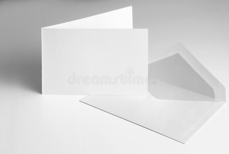 Blank open standing greeting card and envelope. Over grey background stock photo