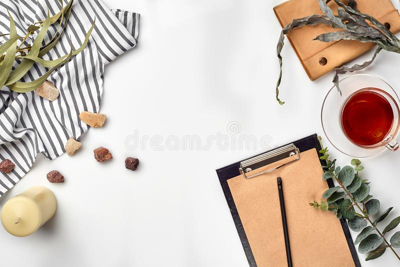 Blank opened notebook with cup of tea on white table. Top view. Writing concept. Still life. Flat lay. Copy space stock photos