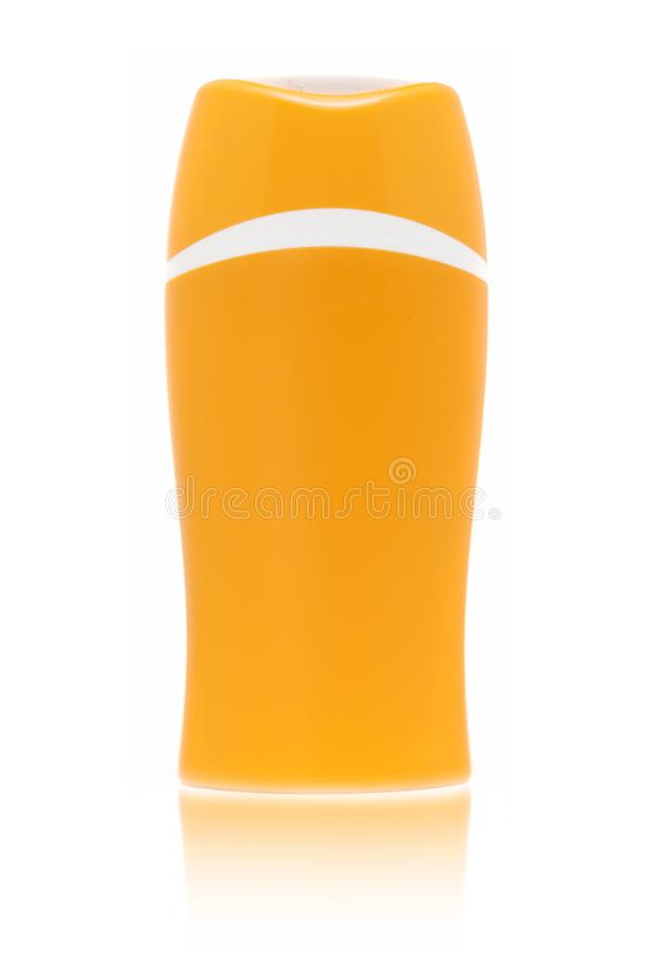A blank orange sun cream bottle isolated on white background with fading reflection. Blank orange sun cream bottle isolated on white background with fading stock photo