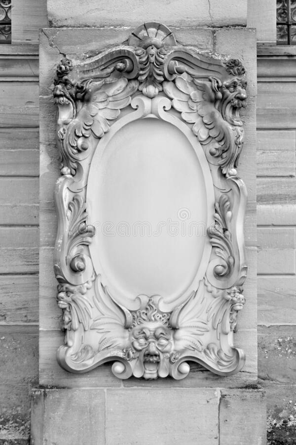 Blank ornate headstone on wall of building royalty free stock image