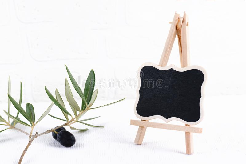 Blank outdoor chalk board stand mockup with olive branch on white brick wall background. Empty street signage or blackboard with stock image
