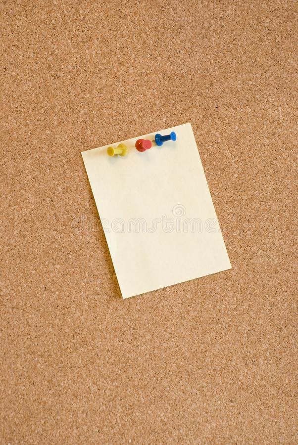 Blank page on corkboard with pins stock image