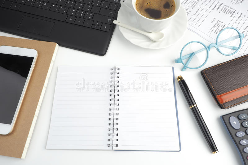 The blank page notebook on white desktop with pen, coffee, laptop, book, calculator, glasses and mobile phone royalty free stock photos