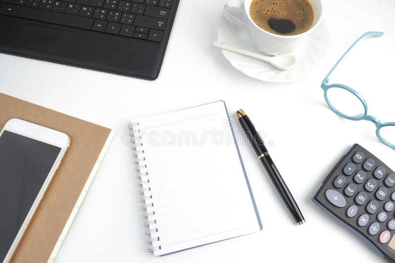 The blank page notebook on white desktop with pen, coffee, laptop, book, calculator, glasses and mobile phone royalty free stock images