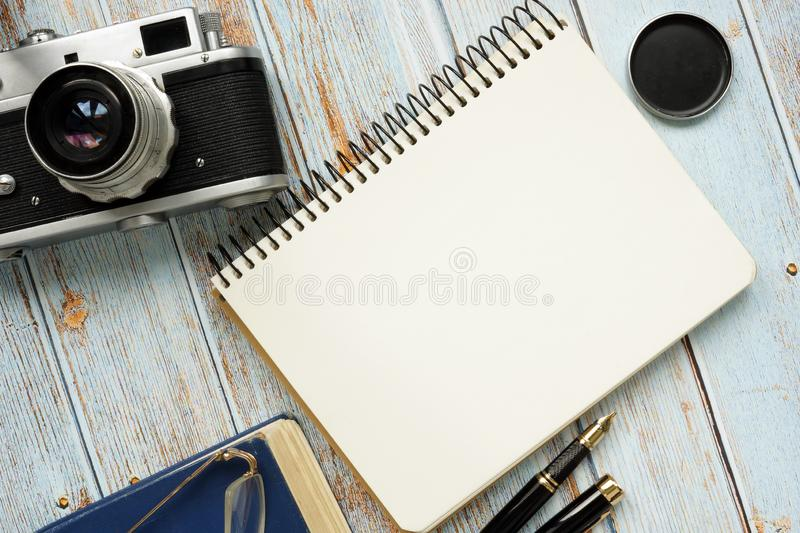 Blank page of notepad and retro photo camera. Top view of desk royalty free stock photography