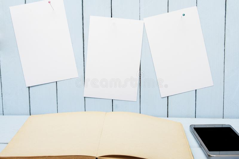 Blank page open book on wooden table. White paper for message on wooden wall royalty free stock photography