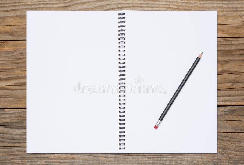 Blank pages of an open sketchbook with a black pencil stock photography