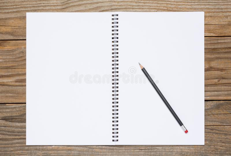 Blank pages of an open sketchbook with a black pencil stock photo