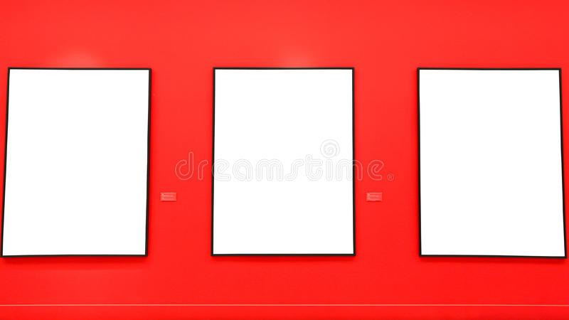 Blank painting frames on red wall. For further photo editing stock images