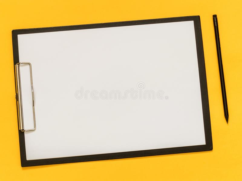 A blank paper on the balck tablet on yellow background. Flat lay. Top view royalty free stock photos