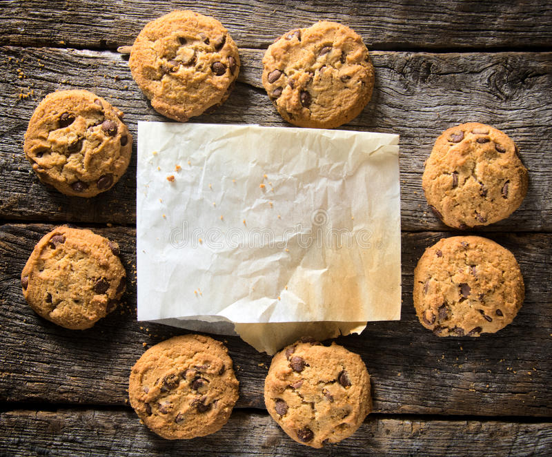 Blank paper and cookies. Blank paper and homemade chip cookies on the wooden table royalty free stock image
