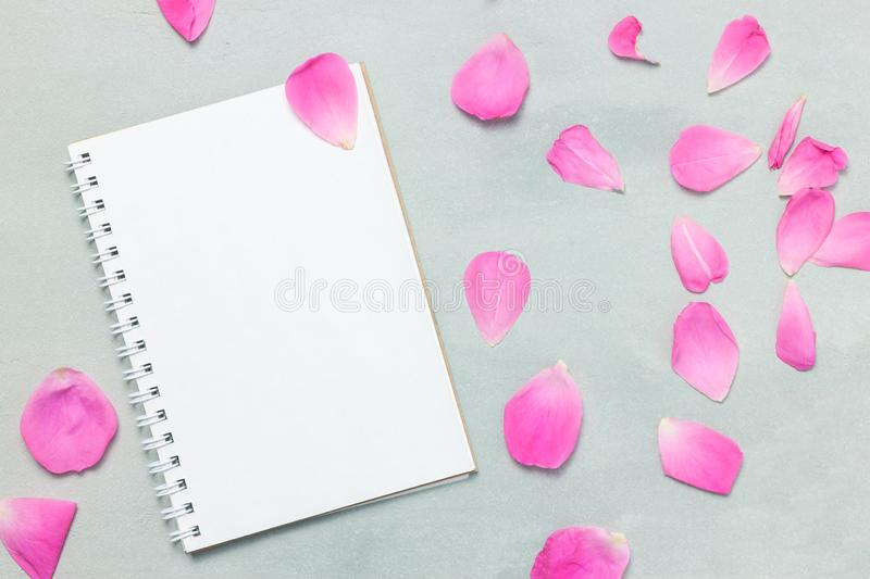 Blank paper and cute pink flowers. Romantic flat lay. cute pink flowers on white wooden table. Top view royalty free stock images