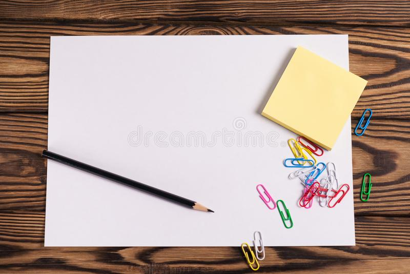 Blank paper and empty yellow square stickers and lot of colored paper clips and one black pencil on old wooden brown worn ta. Blank white paper and empty yellow stock photo