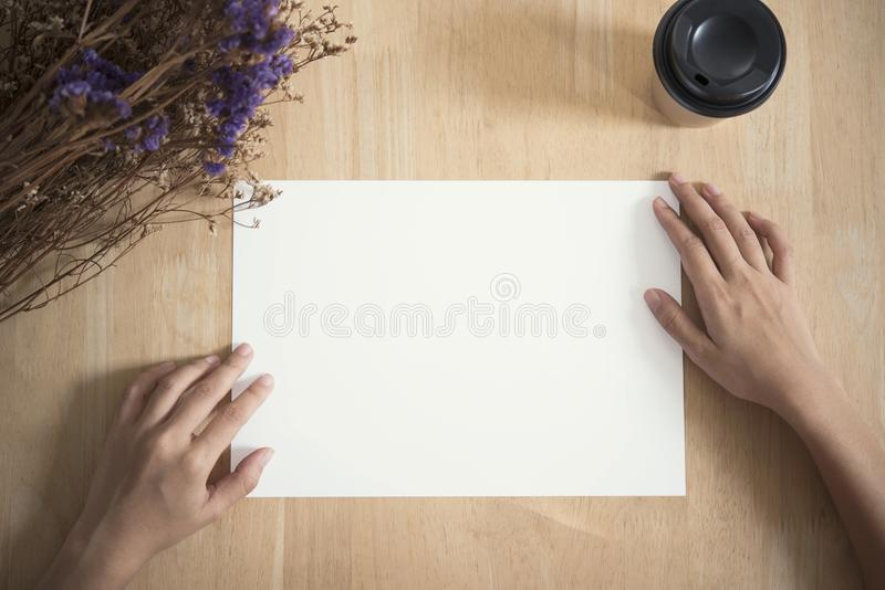 Blank paper A4 flyer for mockup template design logo branding. On wooden background stock photo