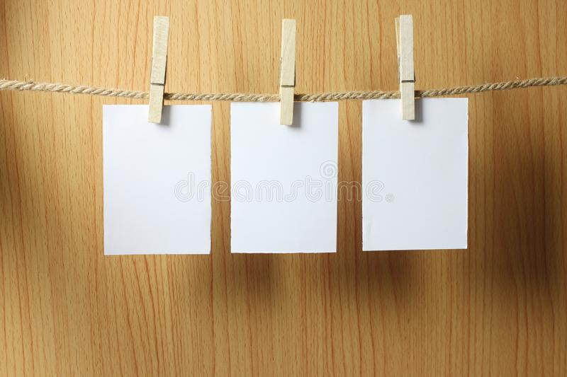 Blank paper hangs on the brown rope with Wooden paper clips on w stock photo