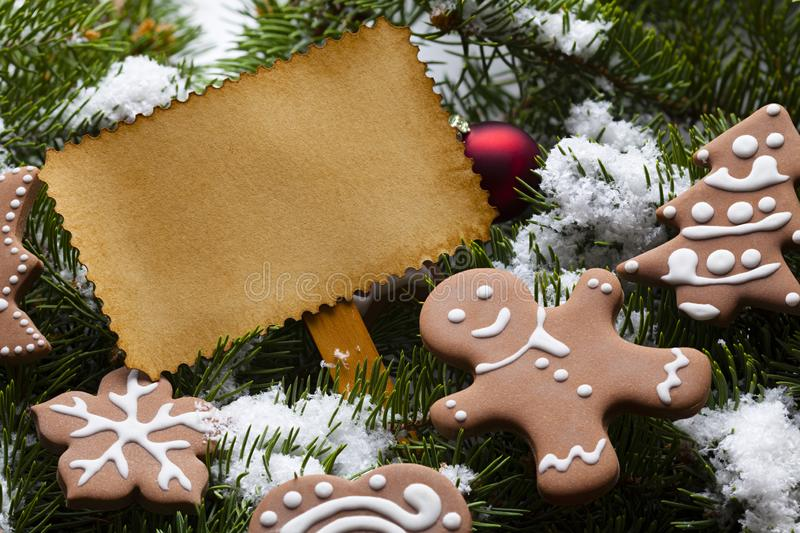 Blank paper card and Christmas gingerbread cookies on snow covered spruce branches. Blank paper label card and Christmas gingerbread cookies on snow covered stock image
