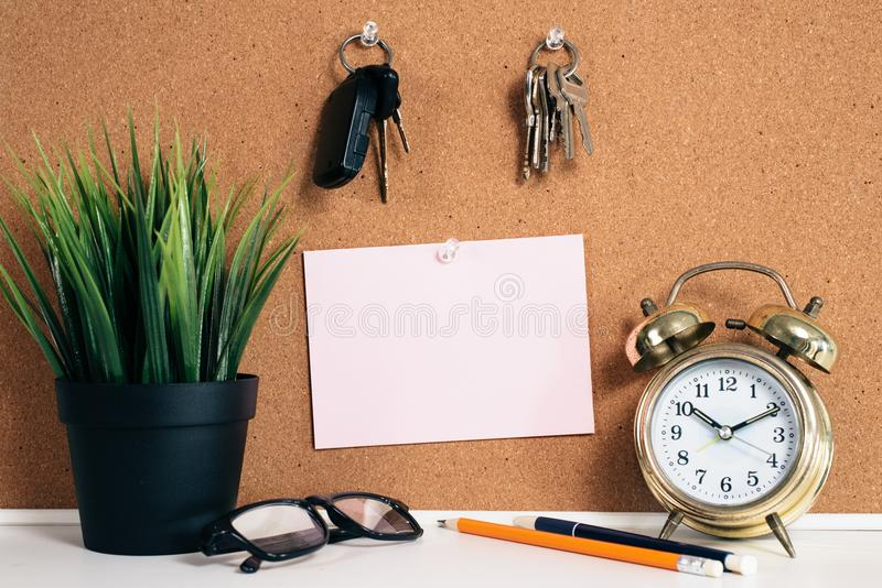 Blank paper note on cork board with car key, golden alarm clock, reading glasses, pen and green plant in pot royalty free stock images