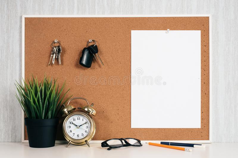 Blank paper note on cork board with car key, golden alarm clock, reading glasses, pen and green plant in pot stock photo