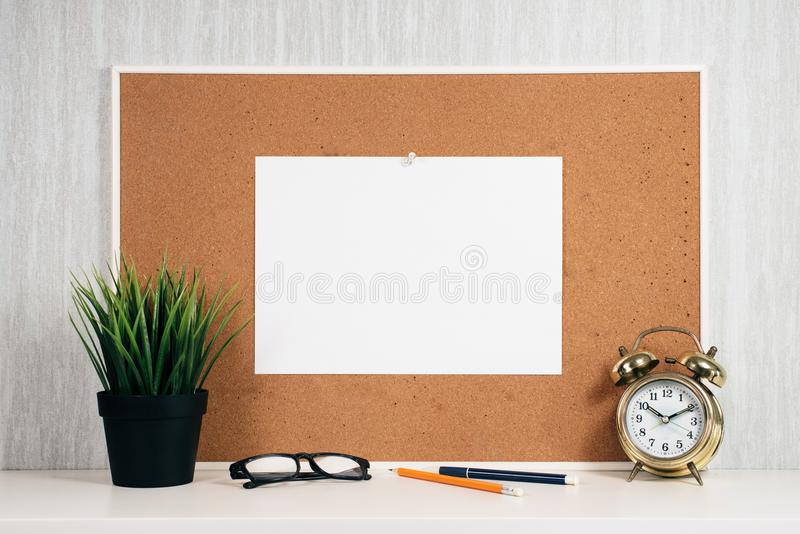 Blank paper note on cork board with golden alarm clock, reading glasses, pen and green plant in pot royalty free stock photos