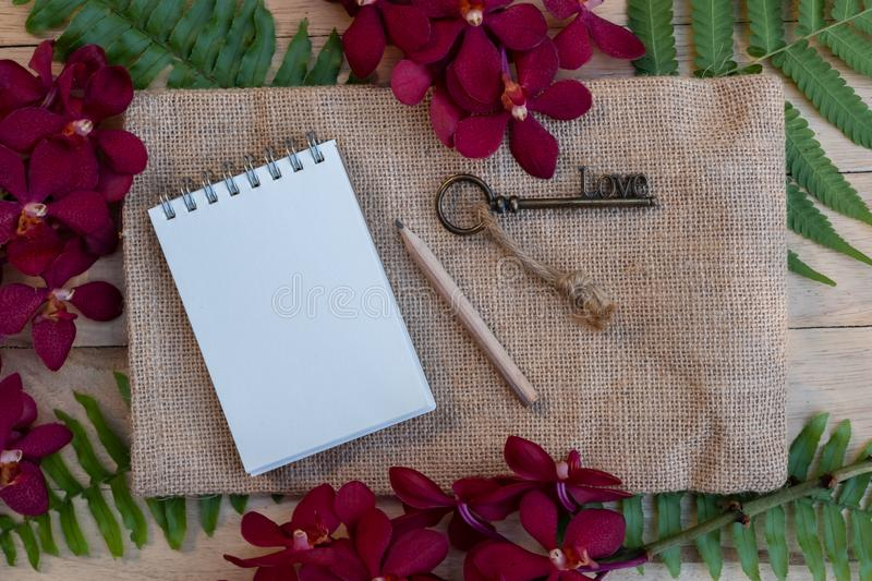 Blank paper note, pencil and vintage key on wooden table decorated with red orchid and green fern. Plan list concept, copy space, notebook, stationary, write stock photos