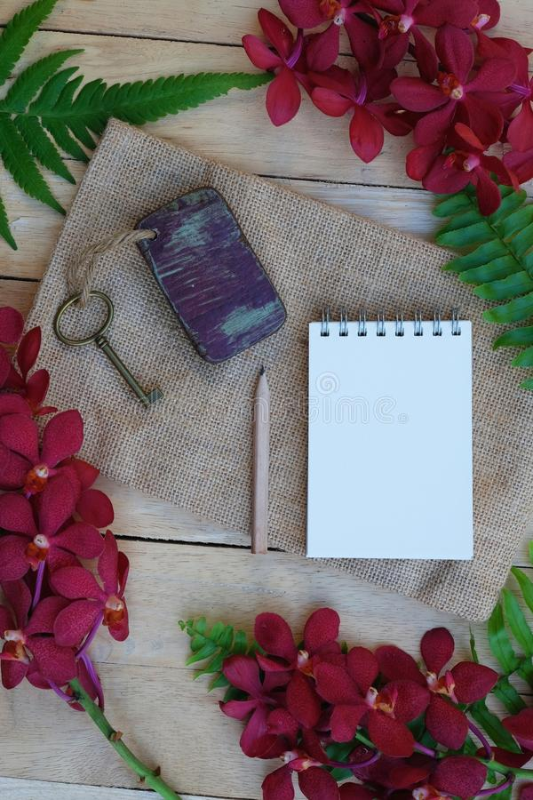 Blank paper note, pencil and vintage key on wooden table decorated with red orchid and green fern. Plan list concept, copy space notebook stationary write text royalty free stock photo