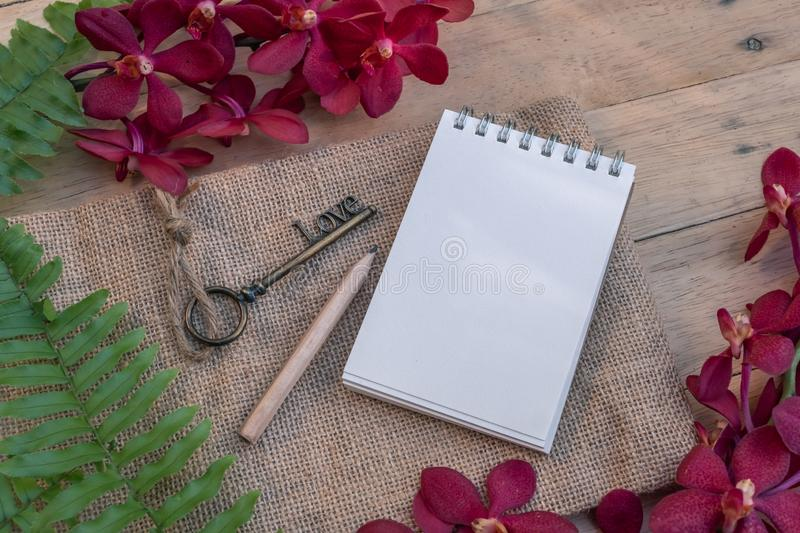 Blank paper note, pencil and vintage key on wooden table decorated with red orchid and green fern. Plan list concept, copy space notebook stationary write text stock photos