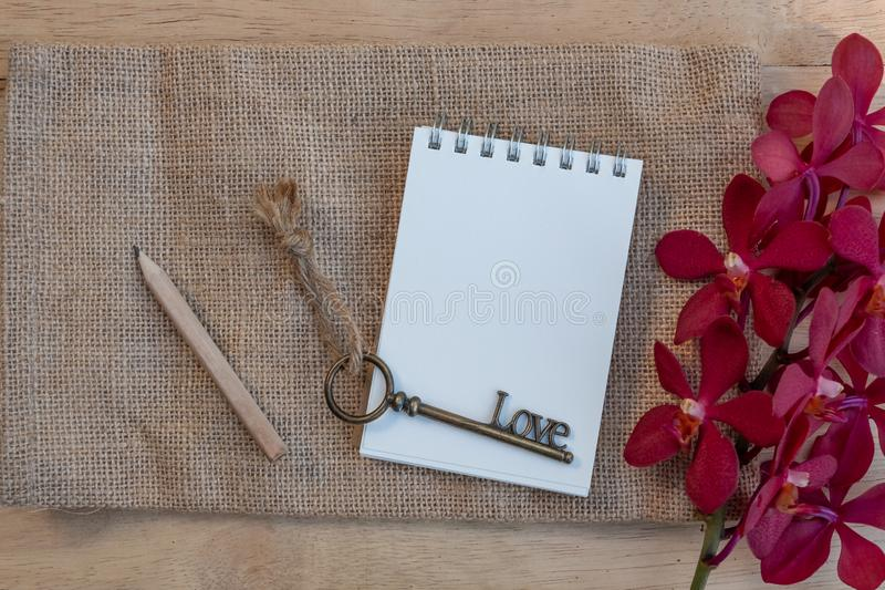 Blank paper note, pencil and vintage key on wooden table decorated with red orchid and green fern. Plan list concept, copy space, notebook, stationary, write royalty free stock photography